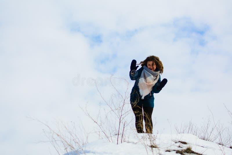 Flicka i vinterställningar på en kulle med hans händer upp begrepp av frihet eller segern arkivfoto