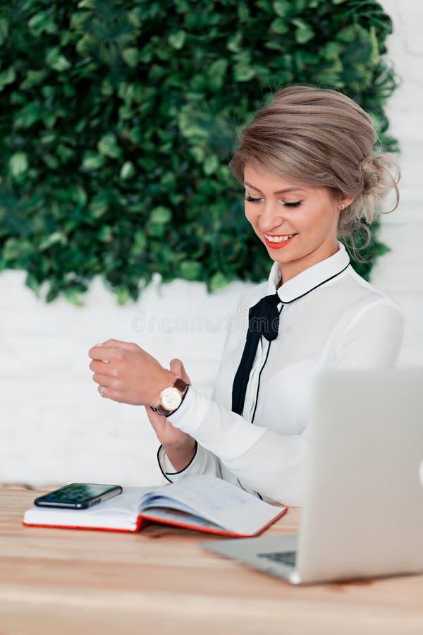 Flicka i vitt blussammanträde på tabellen med bärbara datorn, den röda notepaden och telefonen arkivbilder
