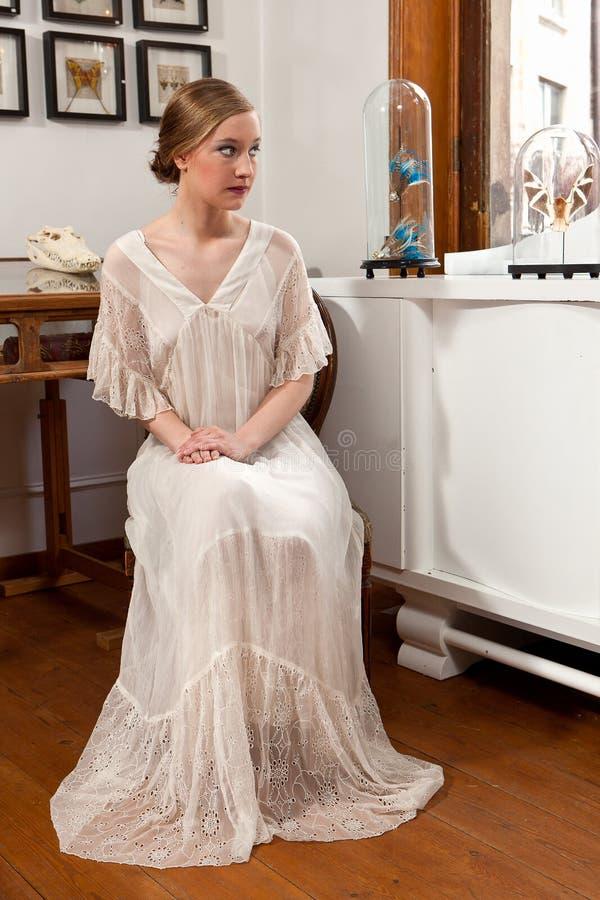 Flicka i vitt klänningsammanträde royaltyfria foton