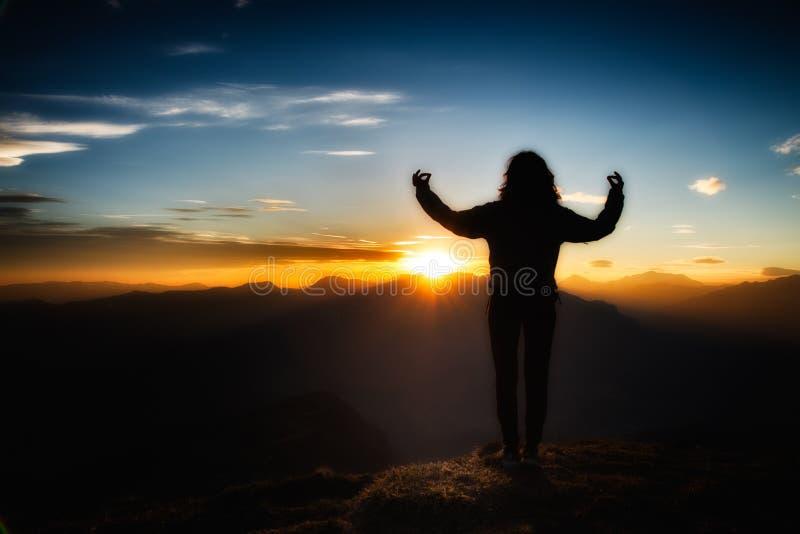 Flicka i yogameditation överst av ett berg på solnedgången royaltyfri bild