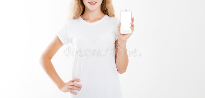 Flicka kvinna i t-skjortan som rymmer mobiltelefonen för tom skärm isolerad på vit bakgrund Armhållsmartphone, kopieringsutrymme fotografering för bildbyråer