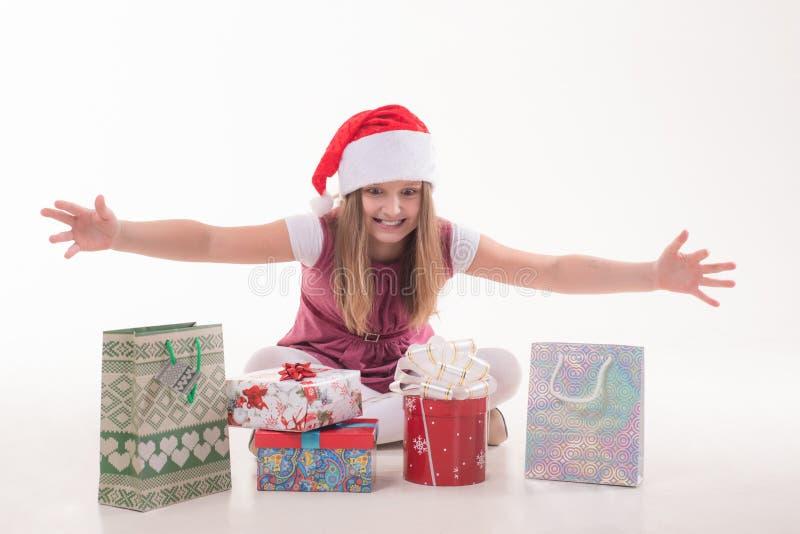 Flicka lite med en gåva i en jultomtenhatt royaltyfri fotografi
