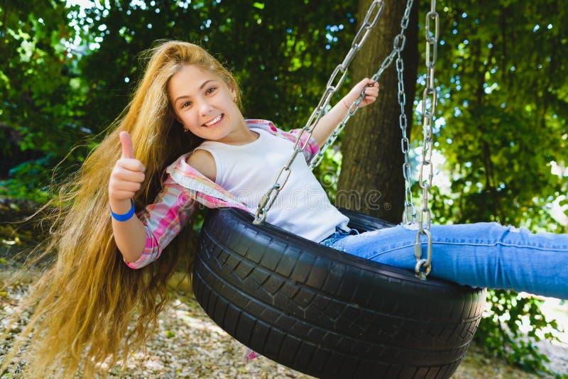 flicka little lekplats Barn som utomhus spelar i sommar Tonåring på en gunga royaltyfri foto