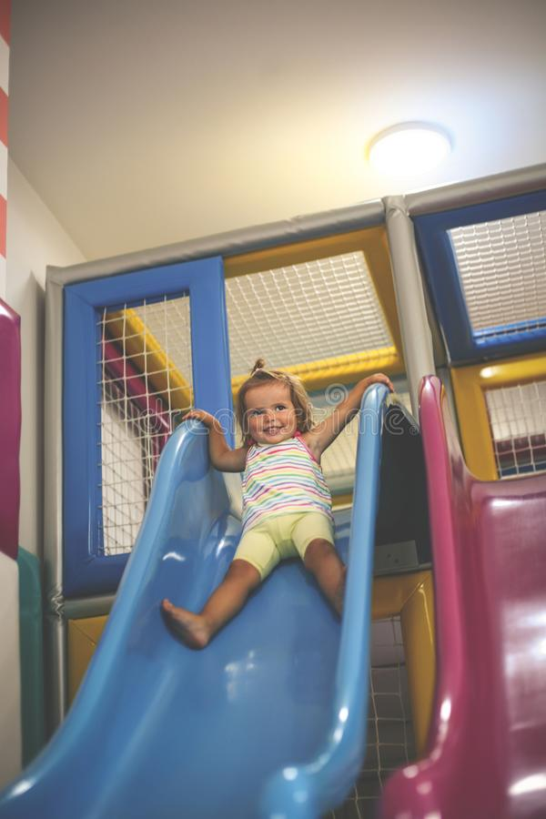 flicka little lekplats Den lyckliga lilla flickan stiger ned från ten royaltyfri fotografi