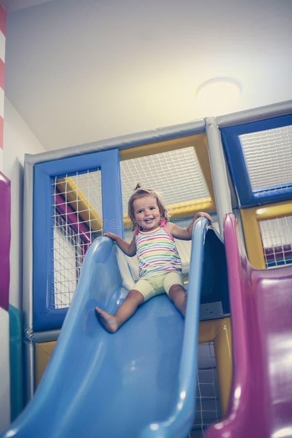 flicka little lekplats Den lyckliga lilla flickan stiger ned från ten arkivfoto