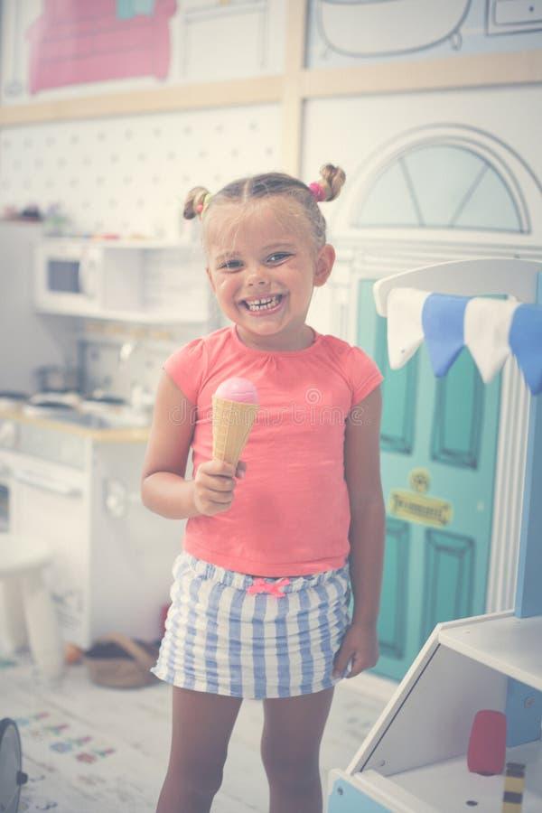 flicka little lekplats Flickaanseende, i lekrum och att äta royaltyfri bild