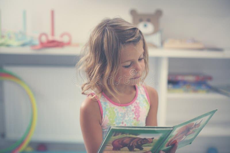 flicka little lekplats Läs- bilderbok för liten flicka arkivfoton