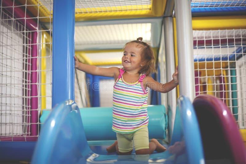 flicka little lekplats Lyckligt liten flickasammanträde på kälken arkivfoton