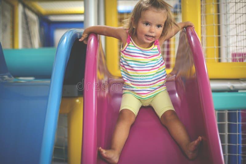 flicka little lekplats Lyckligt liten flickasammanträde på kälken royaltyfri foto