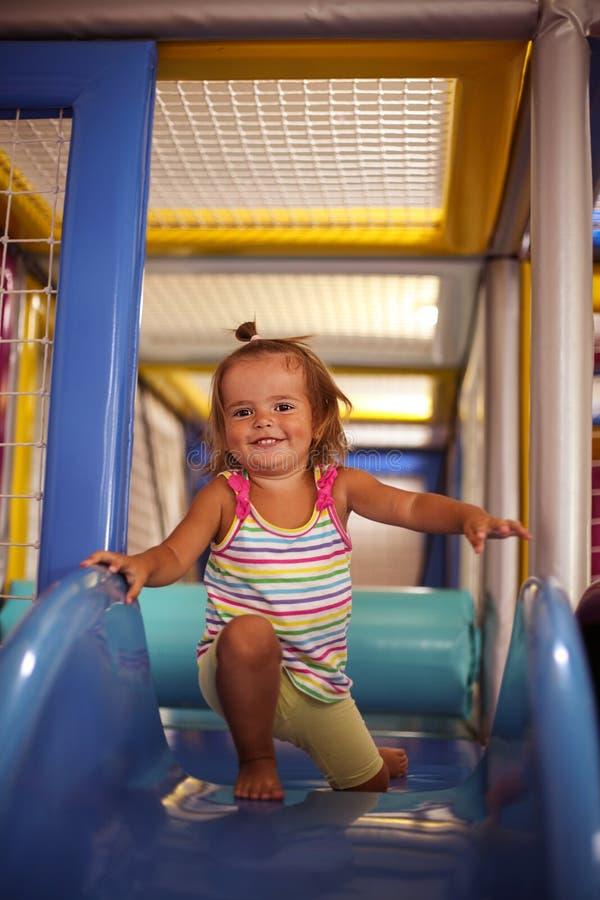flicka little lekplats Lyckligt liten flickasammanträde på kälken royaltyfri bild