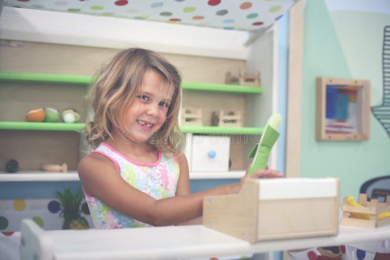 flicka little lekplats Flicka som spelar med barnkassa regis fotografering för bildbyråer
