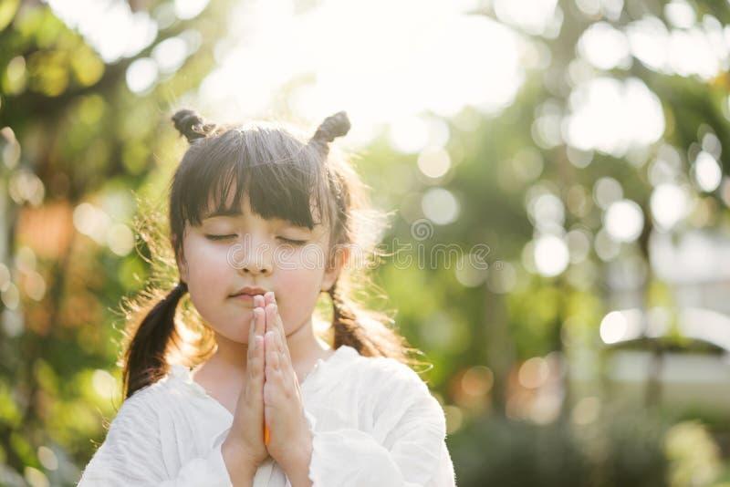 flicka little som ber ungen ber Gest av tro H?nder vek i b?nbegreppet f?r tro, andlighet och religion arkivfoton