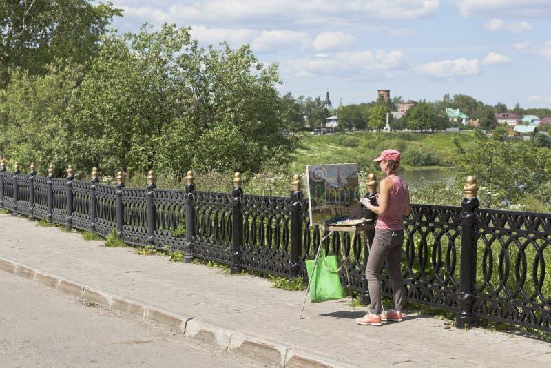 Flicka-målaren målar landskapet av staden av Vologda royaltyfri foto