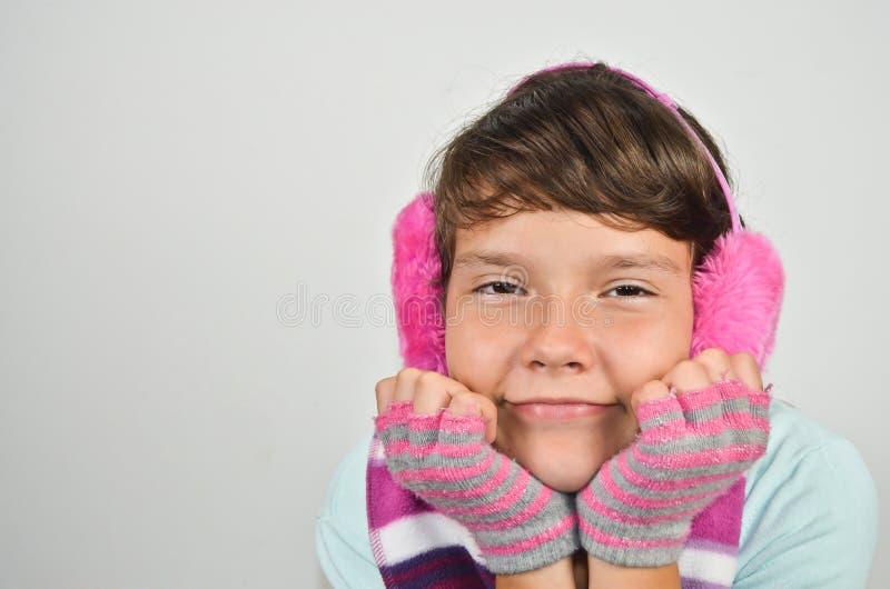 Flicka med öramuffs och klippte handskar fotografering för bildbyråer