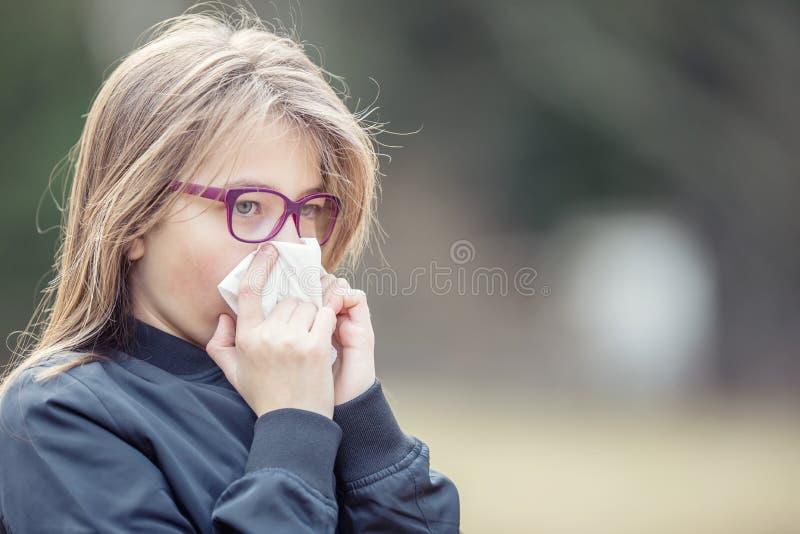 Flicka med allergitecken som blåser näsan Tonårig flicka som använder ett silkespapper i en parkera arkivfoto