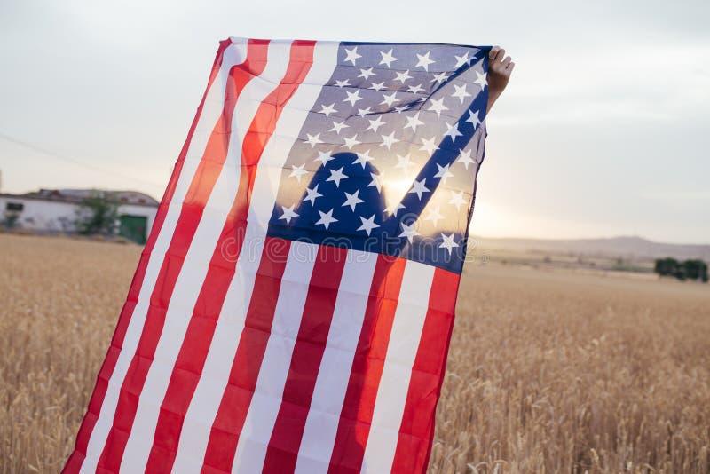Flicka med amerikanska flaggan som ler i solnedgången Playi för ung kvinna arkivbilder