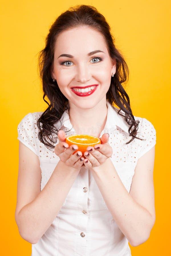 Flicka med apelsinen i händerna royaltyfri fotografi
