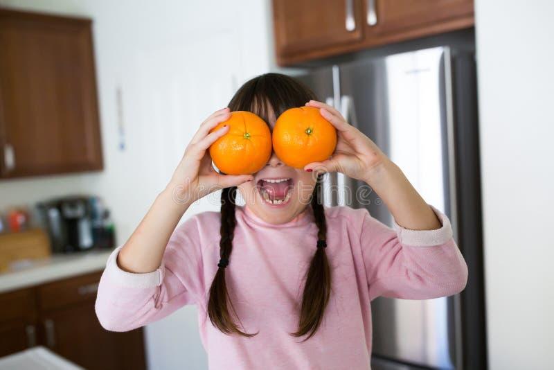 Flicka med apelsiner i kök arkivbilder