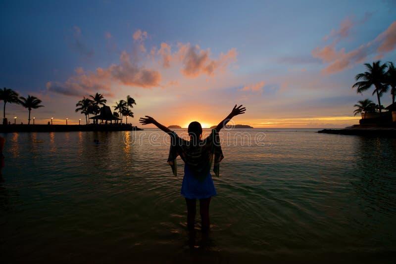 Flicka med armsneda bollen som är öppen på strandsolnedgången royaltyfri bild