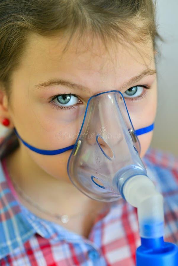 Flicka med astmainhalatorn arkivfoto