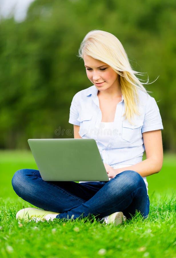 Download Flicka Med Bärbar Datorsammanträde På Det Gröna Gräset Fotografering för Bildbyråer - Bild av gulligt, kvinnlig: 37344093