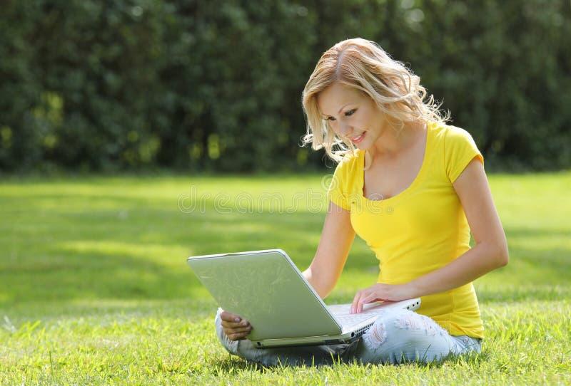 Flicka med bärbara datorn. Blond härlig ung kvinna med anteckningsboksammanträde på gräset. Utomhus-. Solig dag fotografering för bildbyråer