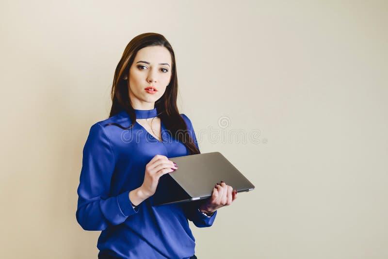 flicka med bärbara datorn på bakgrund av väggen arkivfoto