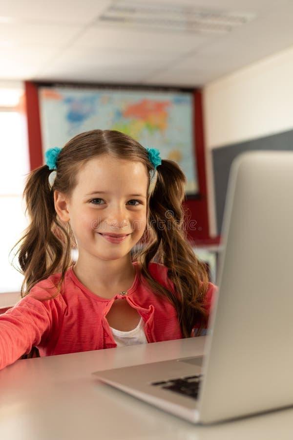 Flicka med bärbara datorn som sitter på skrivbordet i ett klassrum royaltyfri bild