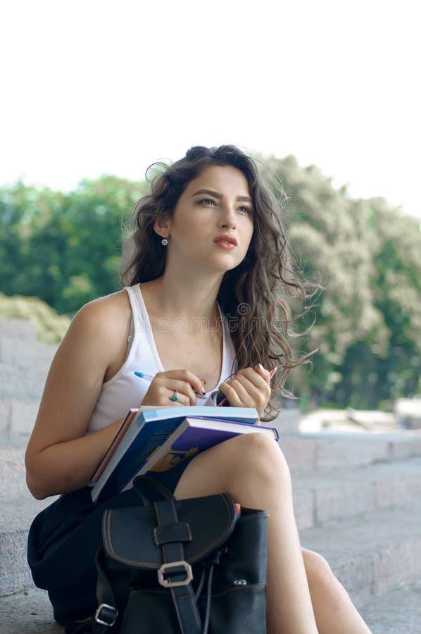 Flicka med böcker som sitter på momenten royaltyfri fotografi