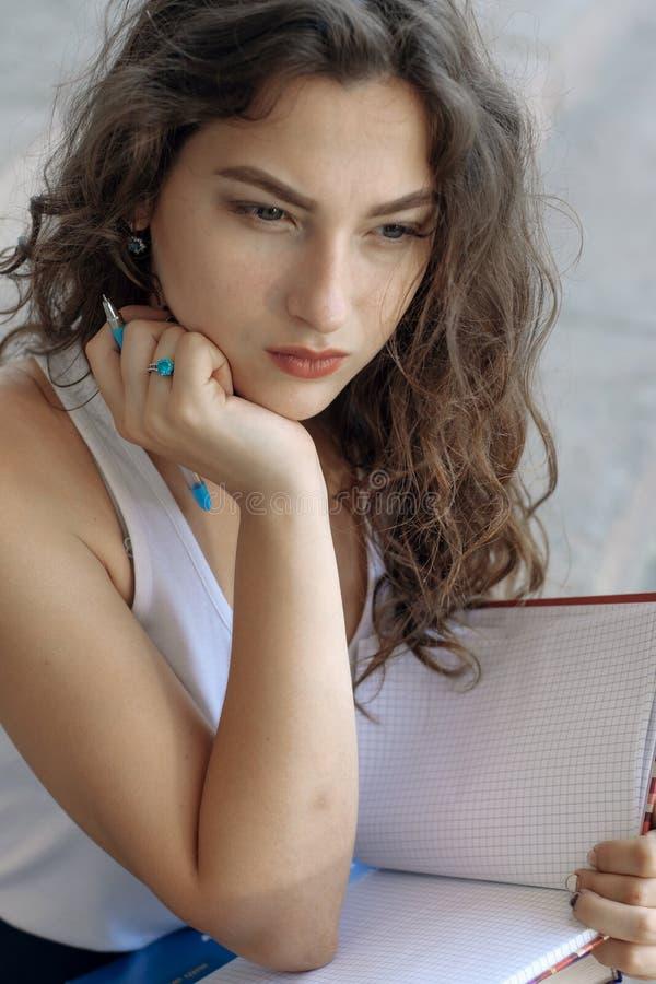 Flicka med böcker som sitter på momenten royaltyfri foto