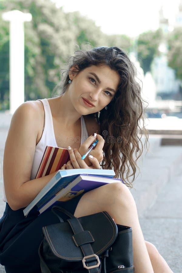Flicka med böcker som sitter på momenten arkivbild