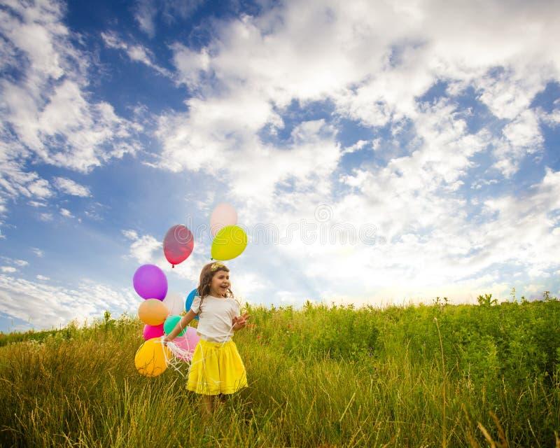 Flicka med ballons mot blå himmel royaltyfri fotografi
