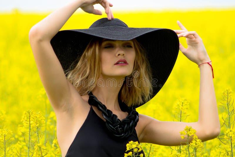 Flicka med behagfulla händer i en stor hatt fotografering för bildbyråer