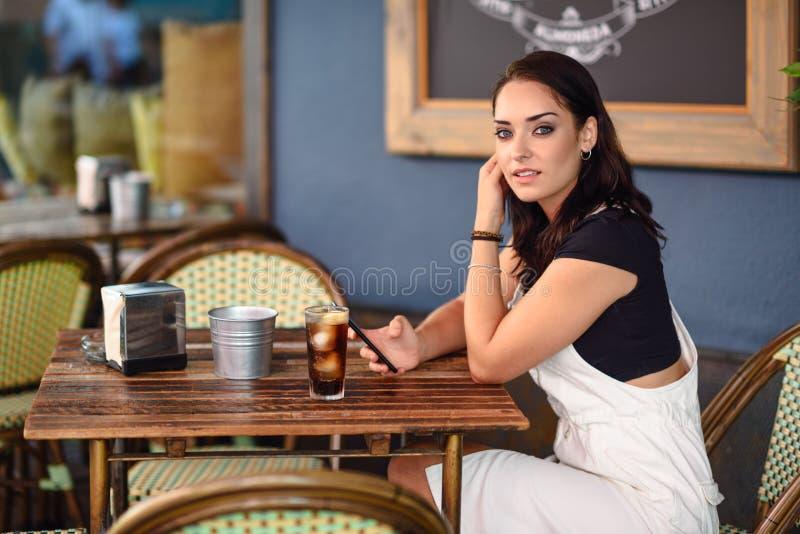 Flicka med blåa ögon som sitter på det stads- kafét genom att använda den smarta telefonen royaltyfria foton