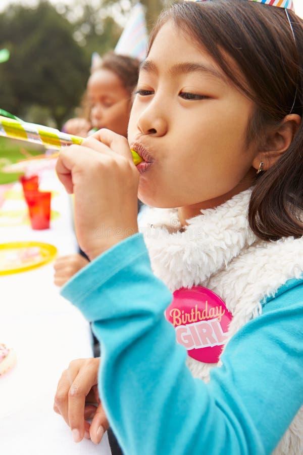Flicka med blåsaren på det utomhus- födelsedagpartiet arkivbild