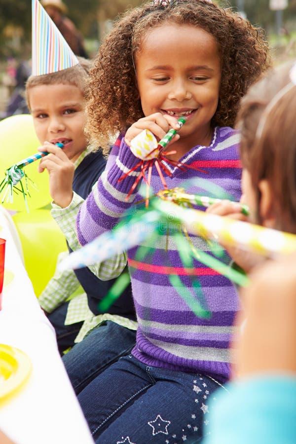 Flicka med blåsaren på det utomhus- födelsedagpartiet royaltyfri foto