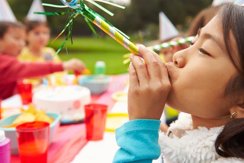 Flicka med blåsaren på det utomhus- födelsedagpartiet arkivfoto