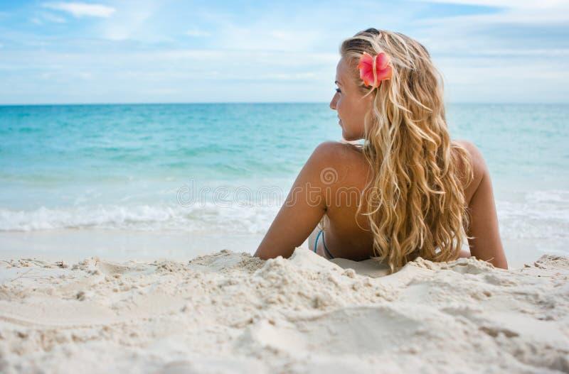 Flicka med blomman på stranden fotografering för bildbyråer