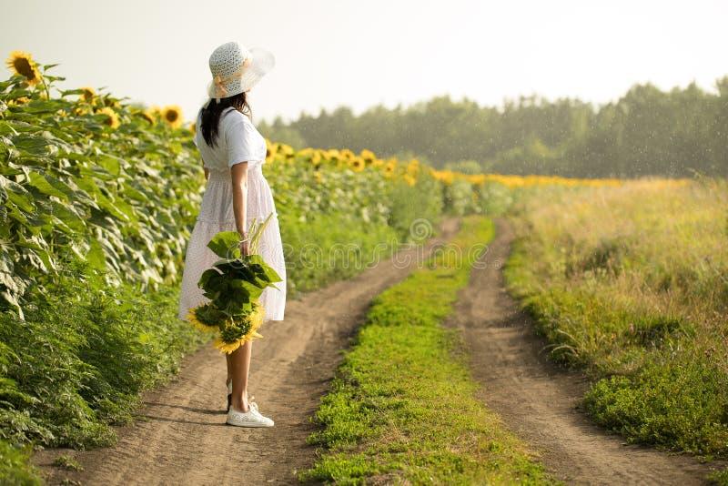 Flicka med blommor flickan går över fältet arkivbild