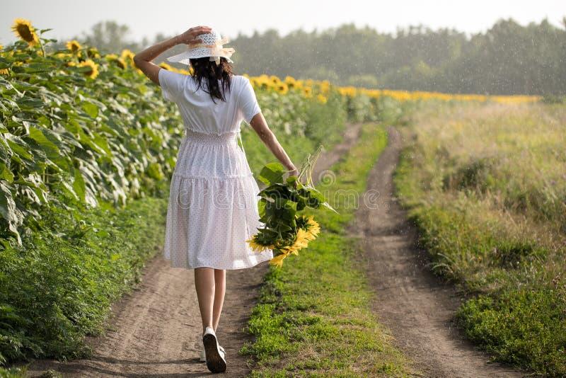 Flicka med blommor flicka som rymmer en bukett av solrosor arkivbilder