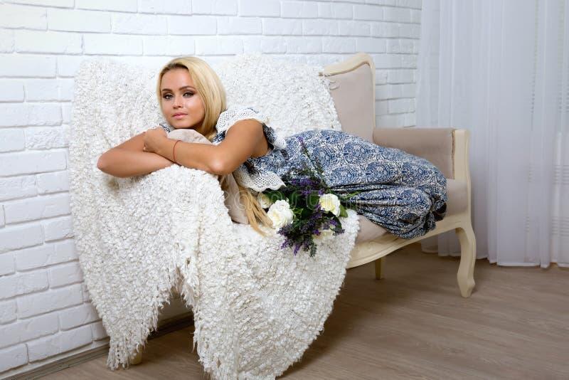 Flicka med blont hår som ligger på soffan royaltyfri bild