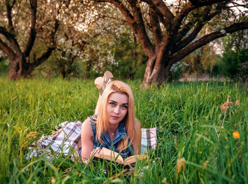 Flicka med boken i parkera royaltyfri fotografi
