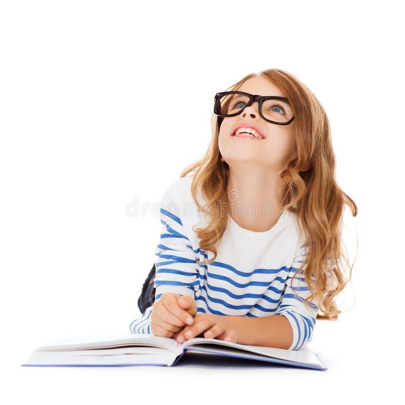 Flicka med boken och glasögon som ligger på golvet fotografering för bildbyråer