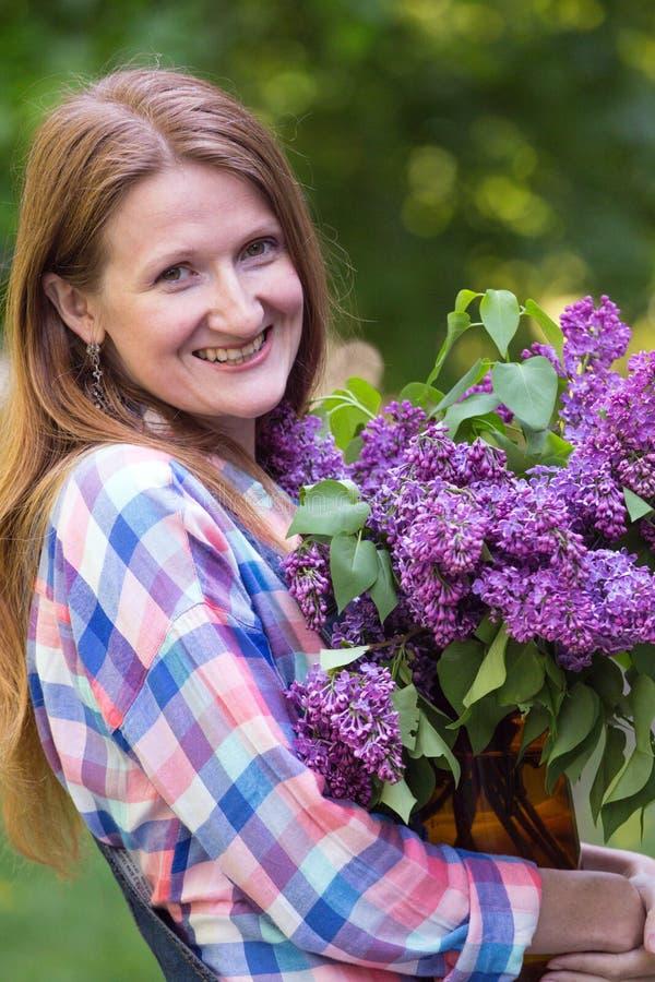 Flicka med buketten av lilor royaltyfri fotografi