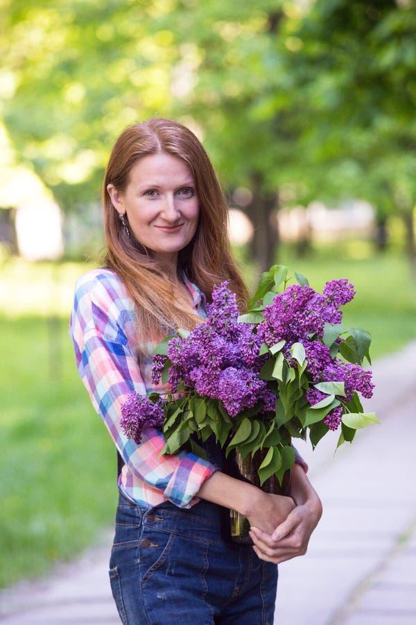 Flicka med buketten av lilor arkivbild