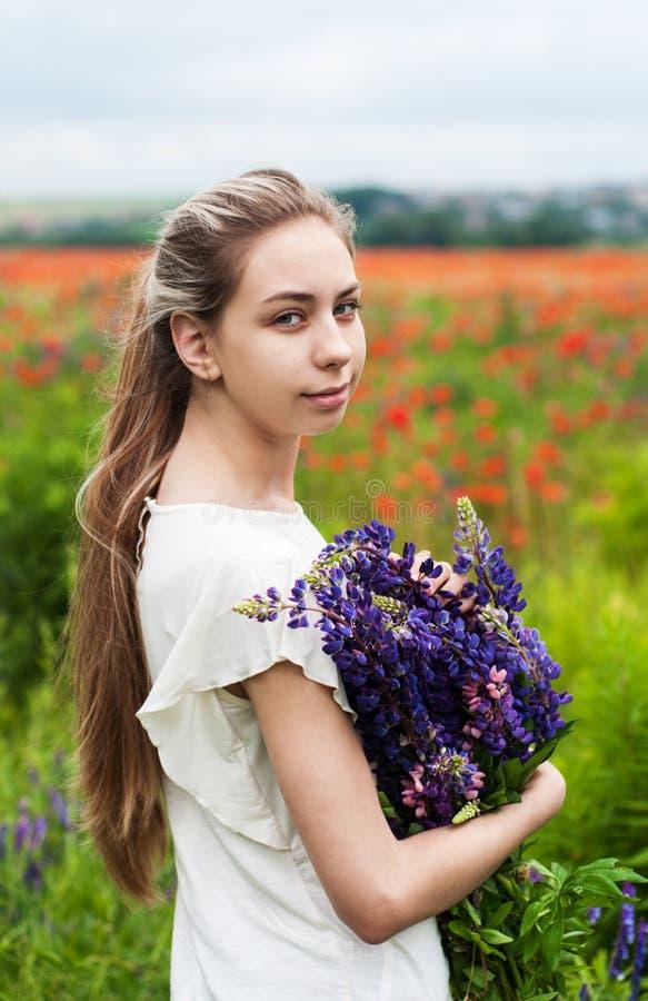 Flicka med buketten av lupineblommor arkivbild