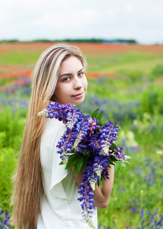 Flicka med buketten av lupineblommor fotografering för bildbyråer