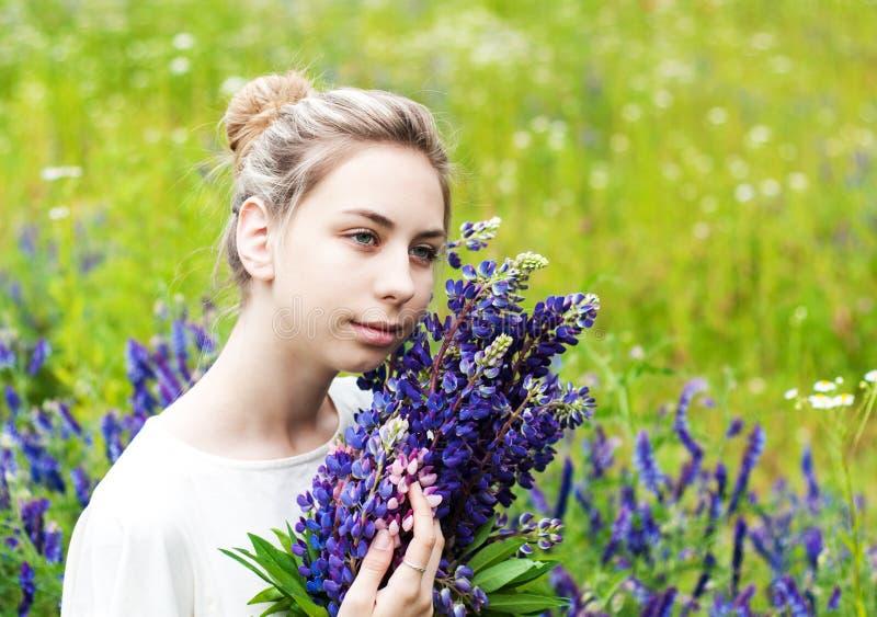 Flicka med buketten av lupineblommor royaltyfria foton