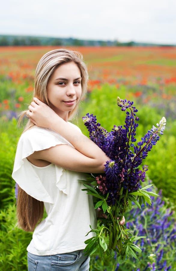 Flicka med buketten av lupineblommor arkivfoton