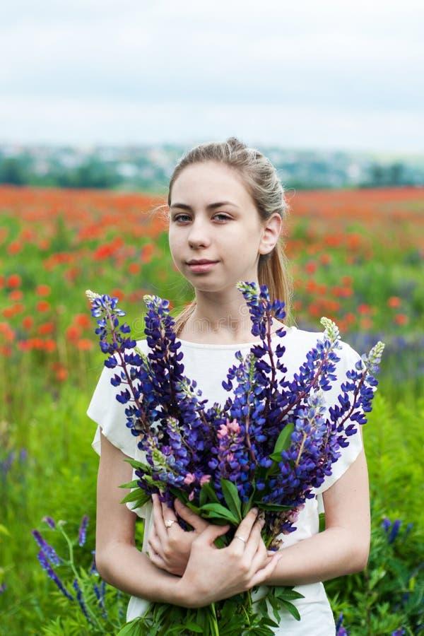 Flicka med buketten av lupineblommor arkivfoto
